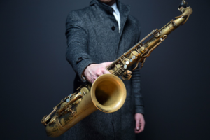 suited man holding Saxophone